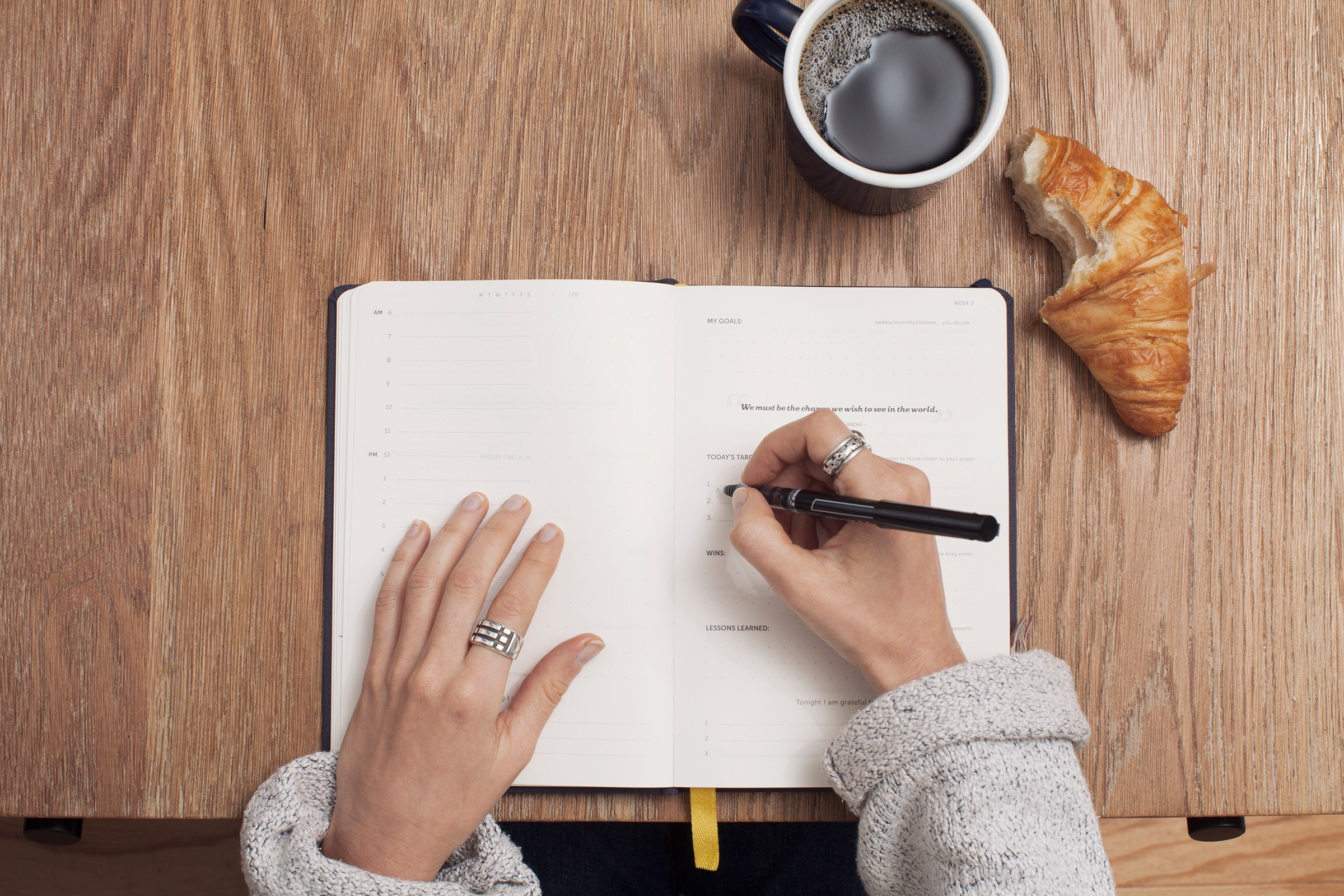 Woman writing in planner with coffee and croissant at a wooden desk.