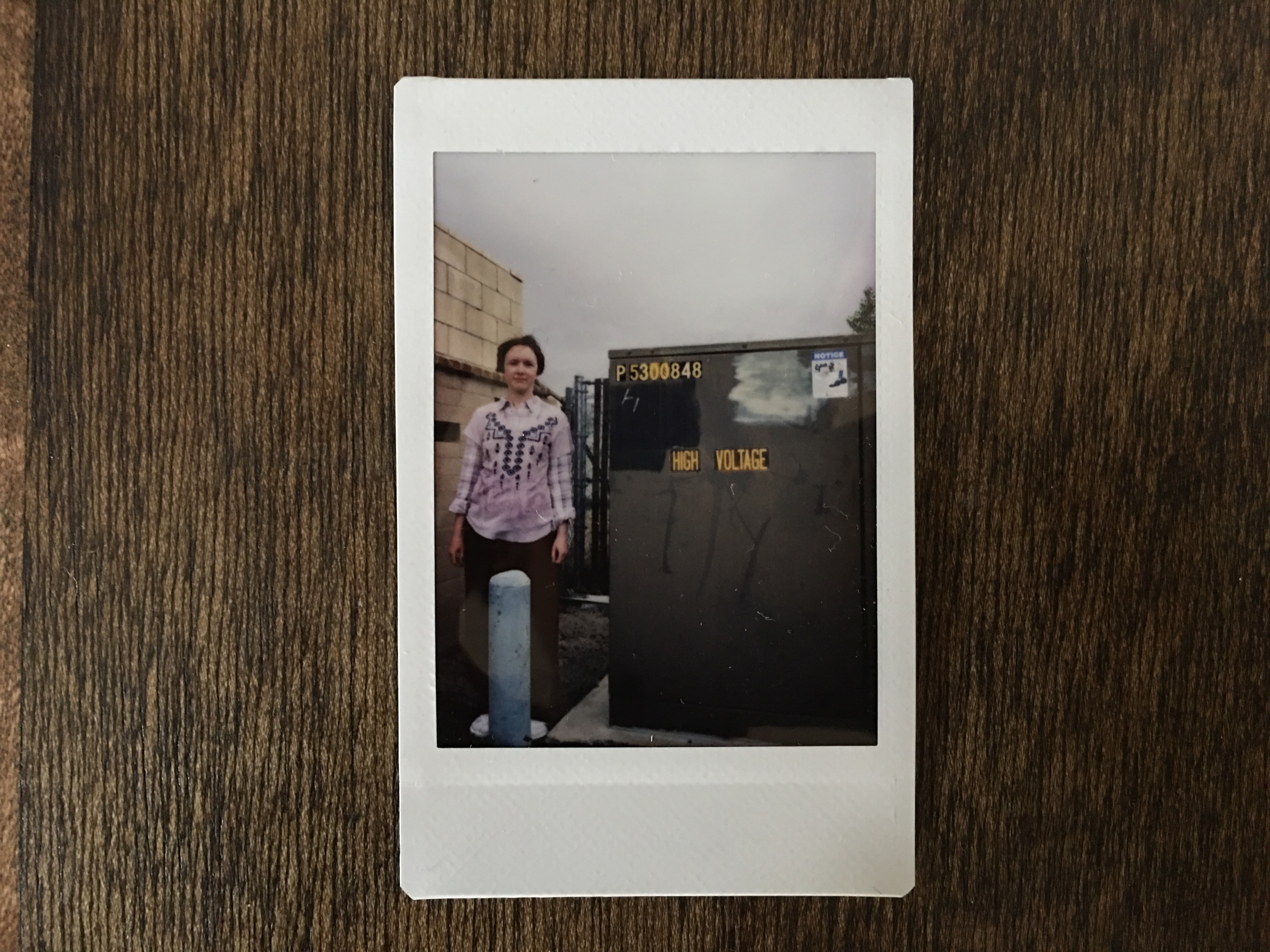"Jessica in a pink shirt standing next to a large electrical box that says, ""High Voltage"""