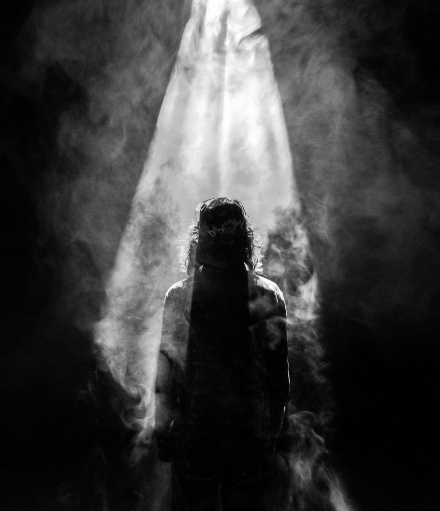 Black and white photo of a man standing in a shaft of light